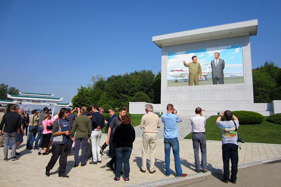 Tour members paying respects to a Mosaic of North Korea's Leaders